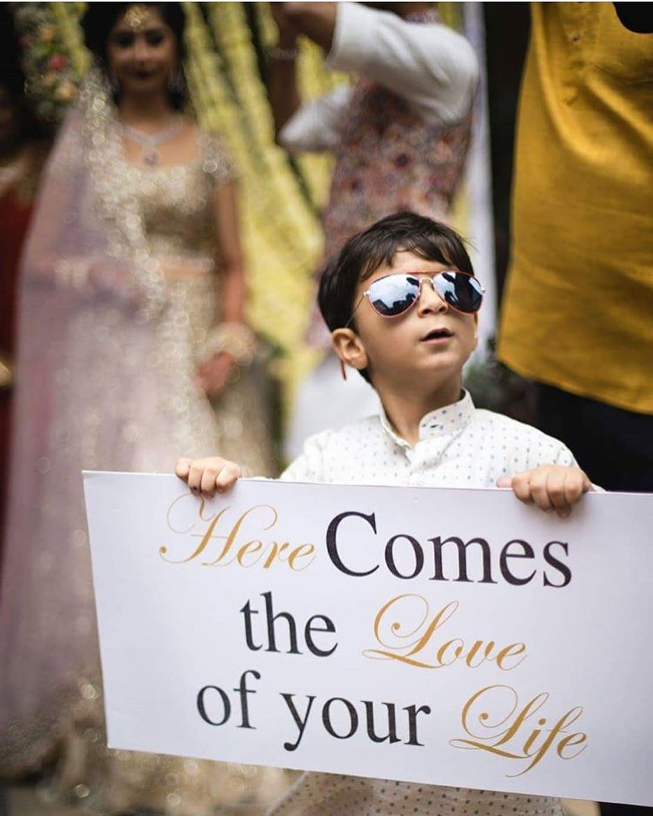 "Cute wedding bride entry idea - nephew holding up sign ""here comes the love of your life"""